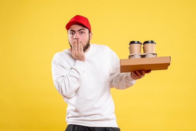Vista frontale del corriere maschio che tiene cibo di consegna e caffè sulla parete gialla