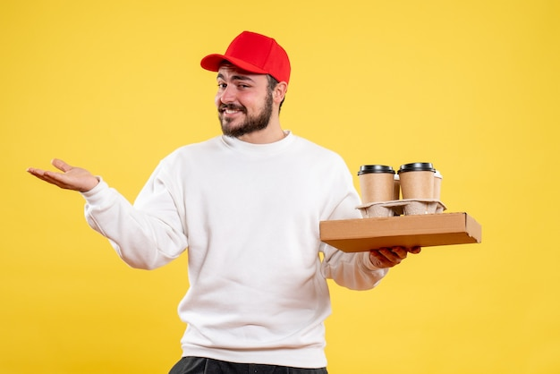 Front view of male courier holding delivery food and coffee on yellow wall