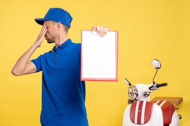 Вид спереди мужской курьер, держащий заметку о файле на желтом цвете, рабочий сервисный велосипед, рабочая эмоция, униформа Бесплатные Фотографии