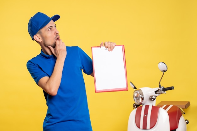Front view male courier holding file note thinking on yellow color worker uniform service bike work emotion