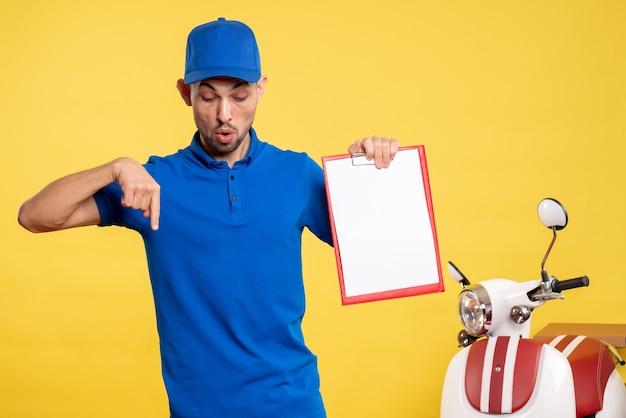 Corriere maschio di vista frontale che tiene la nota del file sulle emozioni di lavoro della bici di servizio uniforme del lavoratore di colore giallo
