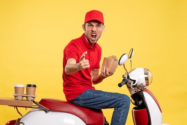 Corriere maschio di vista frontale che tiene poco cibo di consegna che grida sul cibo di servizio uniforme dell'operaio di colore di consegna della bici gialla