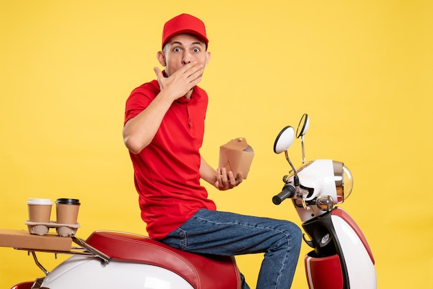 Front view male courier holding little delivery food on yellow bike delivery color work worker uniform food
