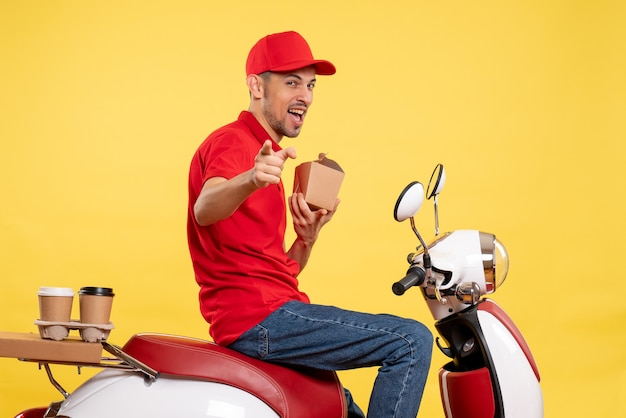 Front view male courier holding little delivery food on a yellow worker bike delivery work uniform service food color