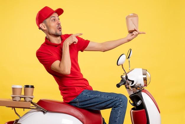 Corriere maschio di vista frontale che tiene poco cibo di consegna sui colori dell'alimento di servizio uniforme del lavoro di consegna della bici dell'operaio giallo