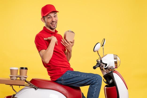 Corriere maschio di vista frontale che tiene poco cibo di consegna sul colore dell'alimento di servizio uniforme del lavoro di consegna del lavoratore giallo