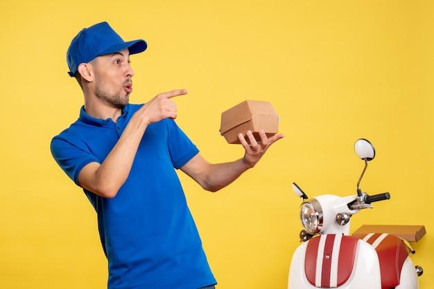 Вид спереди мужчина-курьер, держащий небольшой пакет с едой на желтой форме службы работы, велосипед, цвет работника по доставке работы