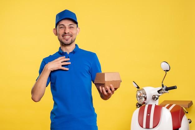 Вид спереди мужской курьер, держащий небольшой пакет с едой на желтой рабочей униформе, доставка работы на велосипеде