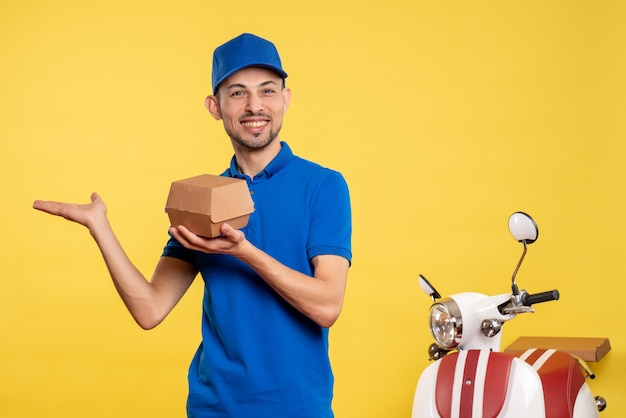 Front view male courier holding little food package on a yellow job colors service work delivery uniform bike worker