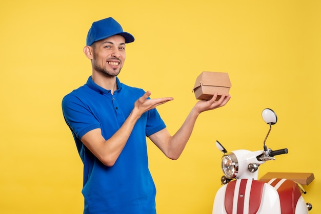Front view male courier holding little food package on the yellow job colors service work delivery uniform bike worker