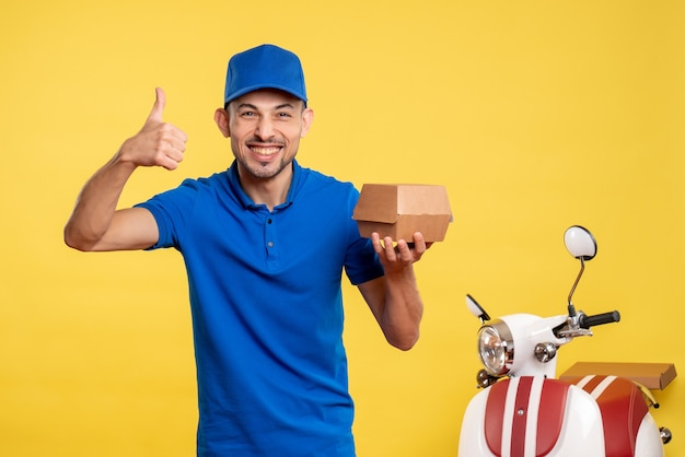 Front view male courier holding little food package on yellow job colors service work delivery uniform bike worker