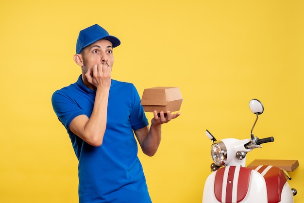 Front view male courier holding little food package on yellow job colors service work delivery uniform bike