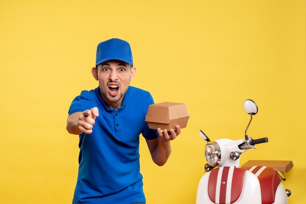 Front view male courier holding little food package on yellow job colors service work delivery uniform worker