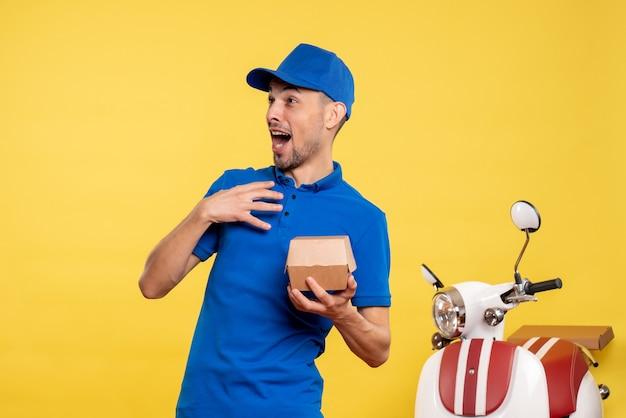 Corriere maschio di vista frontale che tiene piccolo pacchetto di cibo sul colore giallo dell'operaio di consegna del lavoro della bici di servizio di lavoro giallo