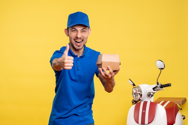 Front view male courier holding little food package on yellow job service uniform bike work delivery worker color