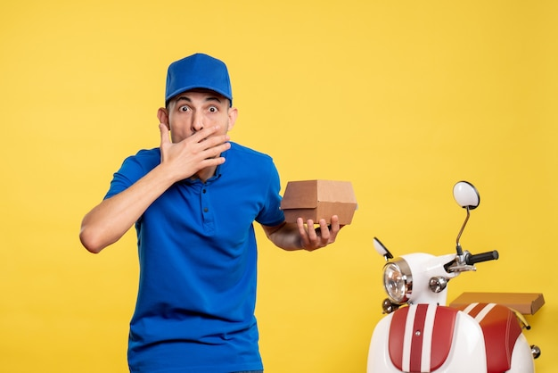 Front view male courier holding little food package on yellow job service work delivery uniform bike worker