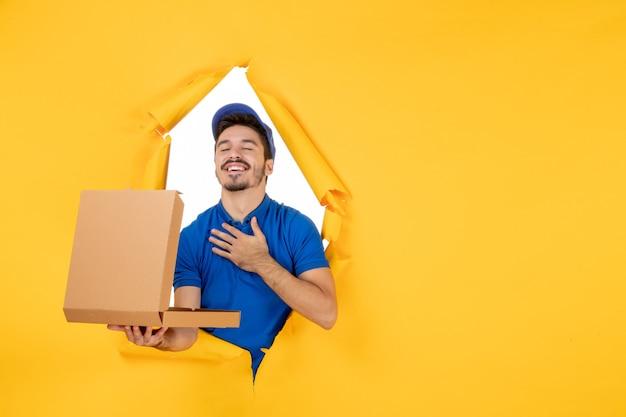黄色のスペースに開いたピザボックスを保持している正面図男性宅配便