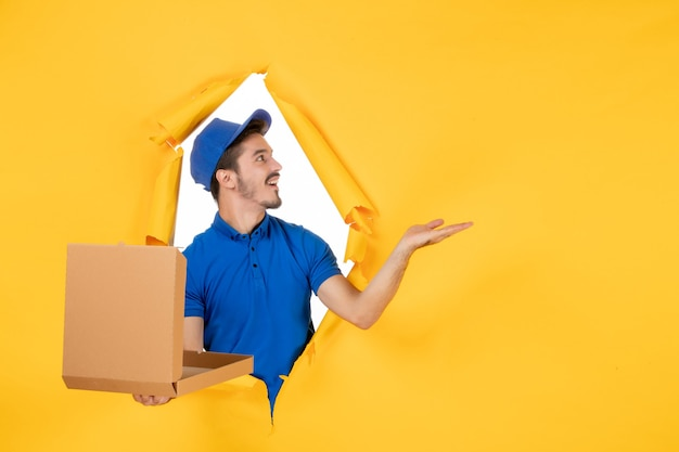 Front view male courier holding opened pizza box on a yellow space