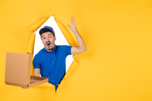 Front view male courier holding opened pizza box on the yellow space