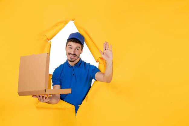 Front view male courier holding opened pizza box on yellow space