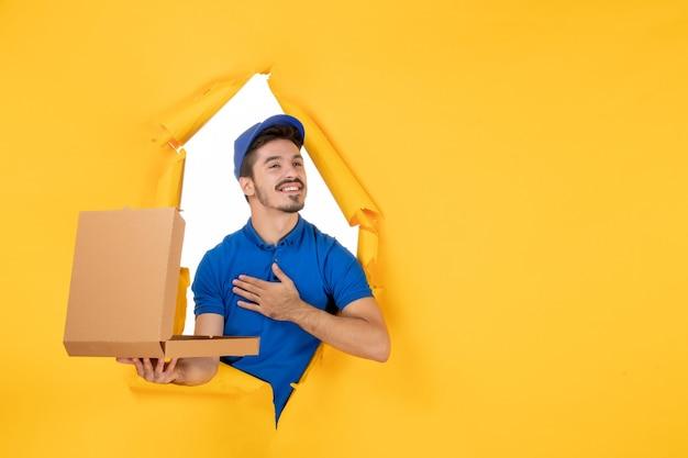 Corriere maschio di vista frontale che tiene la scatola della pizza aperta su spazio giallo