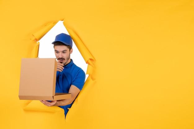 黄色のスペースにピザボックスを保持している正面図男性宅配便