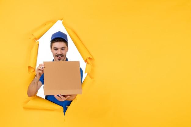 Corriere maschio di vista frontale che tiene la scatola della pizza su spazio giallo