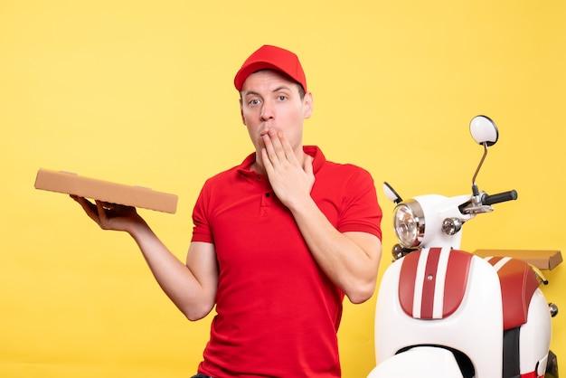 Corriere maschio di vista frontale che tiene la scatola della pizza sul colore giallo della bici dell'uniforme del lavoratore di lavoro di consegna del lavoro