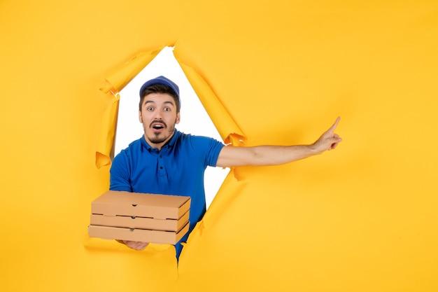 明るい黄色のスペースにピザの箱を保持している正面図男性宅配便