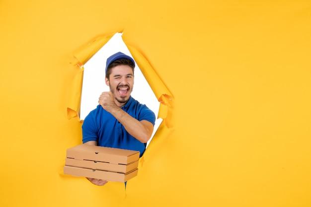 Вид спереди мужской курьер, держащий коробки для пиццы на желтом столе, цветной работник службы доставки, служба доставки еды, униформа, работа