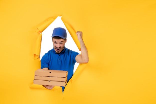 노란색 공간에 피자 상자를 들고 있는 전면 보기 남성 택배
