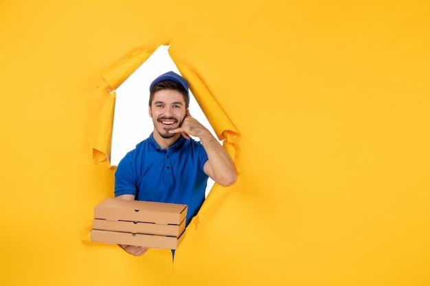 Вид спереди мужской курьер, держащий коробки для пиццы на желтом пространстве