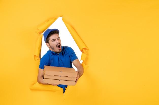 黄色のスペースにピザの箱を保持している正面図男性宅配便
