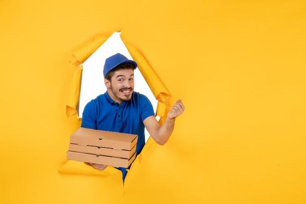 Corriere maschio vista frontale che tiene scatole per pizza su spazio giallo