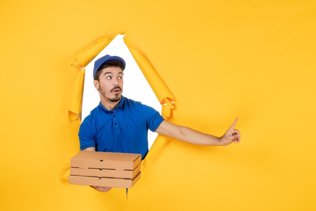 Front view male courier holding pizza boxes on yellow space