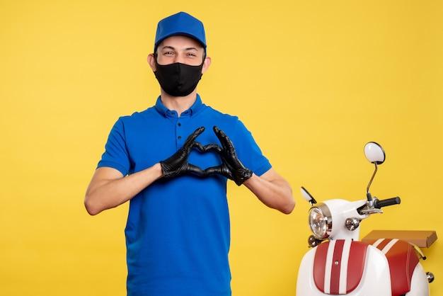 Курьер-мужчина в черной маске и синей униформе, вид спереди, на желтой пандемии, работа в униформе covid- service