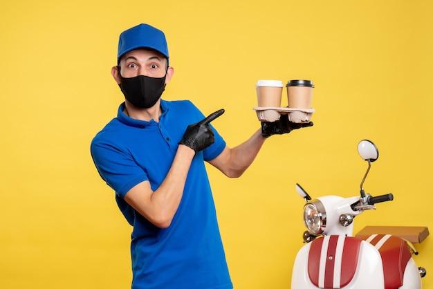 노란색 작업 covid- 대유행 배달 유니폼 작업 서비스에 커피를 들고 검은 마스크에 전면보기 남성 택배