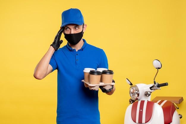 노란색 작업 covid- 대유행 서비스 배달 유니폼 작업에 커피를 들고 검은 마스크에 전면보기 남성 택배