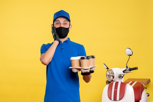 Вид спереди мужчина-курьер в черной маске, держащий кофе на желтой работе по доставке пандемии, covid- service uniform work