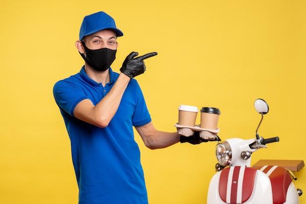 노란색 배달 작업 covid- 대유행 서비스 유니폼에 커피를 들고 검은 마스크에 전면보기 남성 택배