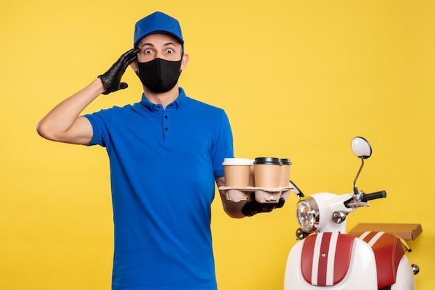 노란색 배달 작업 covid 유행성 작업 서비스 유니폼에 커피를 들고 검은 마스크에 전면보기 남성 택배