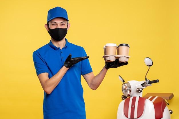 노란색 배달 작업 covid- 전염병 작업 유니폼에 커피를 들고 검은 마스크에 전면보기 남성 택배