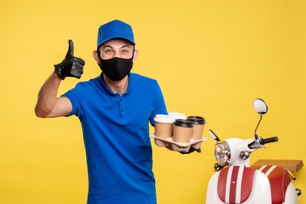 Вид спереди мужчина-курьер в черной маске, держащий кофе на желтой доставке.