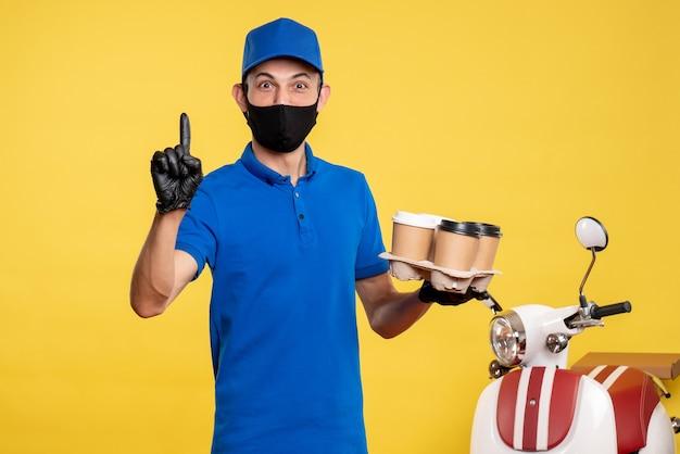 Вид спереди мужчина-курьер в черной маске держит кофе на желтой работе covid- служба доставки пандемии