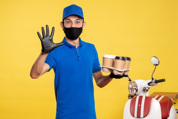 노란색 작업 covid- 전염병 배달 유니폼 작업에 커피를 들고 검은 마스크에 전면보기 남성 택배