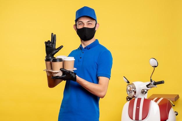 Вид спереди мужчина-курьер в черной маске с кофе на желтой работе covid- пандемия службы доставки униформа