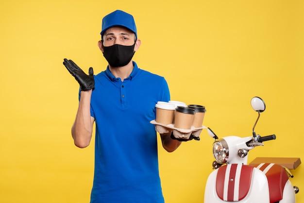 노란색 작업 covid- 대유행 서비스 유니폼 작업에 커피를 들고 검은 마스크에 전면보기 남성 택배