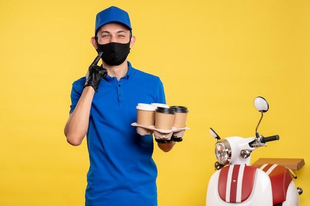 노란색 작업 배달 작업 covid 유행성 서비스에 커피를 들고 검은 마스크에 전면보기 남성 택배