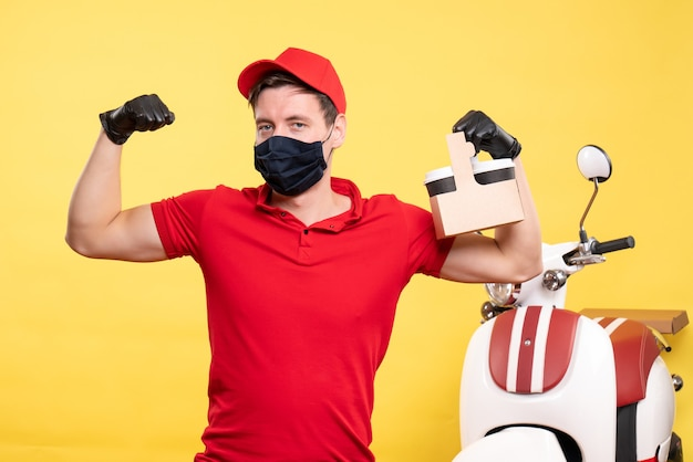 黄色い仕事ウイルス covid-配信制服作業サービスにコーヒー カップと黒いマスクの正面の男性宅配便