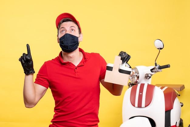 黄色い労働者ウイルスにコーヒーカップを付けた黒いマスクの正面男性宅配便